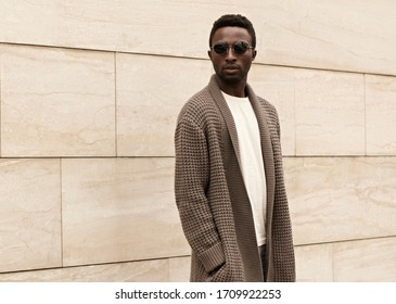 Stylish african man model wearing brown knitted cardigan, sunglasses on city street over brick wall background