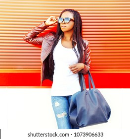 Stylish african woman with bag in city over red background