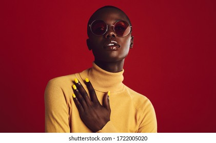 Stylish african woman posing in sunglasses. Female model with buzz cut looking at camera on red background.