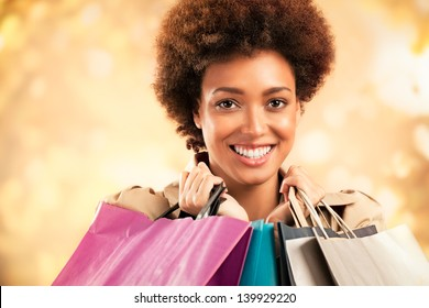 Stylish African-American woman posing in front of a glittering gold background ang holding shopping bags.