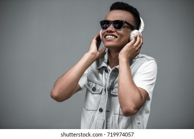 Stylish Afro American guy in headphones and sun glasses is listening to music and smiling, on gray background