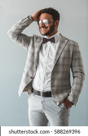 Stylish Afro American guy in suit, bow tie and sun glasses is smoothing his hair and smiling, on gray background
