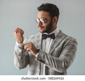 Stylish Afro American guy in suit, bow tie and sun glasses is adjusting cuff, on gray background