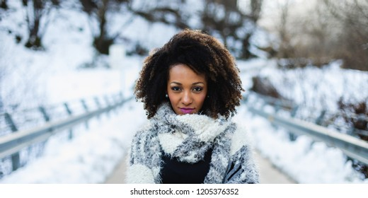 Stylish afro hair woman winter portrait. Female wearing warm wool scarf.