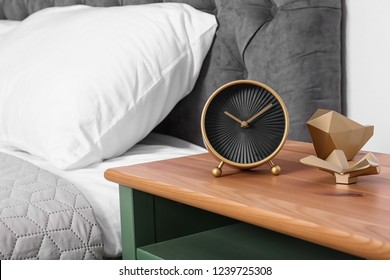 Stylish alarm clock and decor on nightstand in bedroom. Space for text
