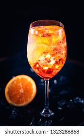 Stylish alcoholic aperol spritz trendy cocktail with orange slice on black background. Vertical