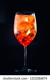 Stylish alcoholic aperol spritz trendy cocktail with orange slice on black background. Champagne cocktail.
