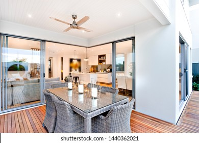 A stylish all- wicker dining table on the porch with wicker chairs and a wicker table with a glass top and stylish candles on the table top, separated from the house with glass sliding doors