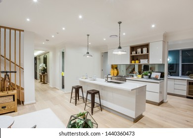 Stylish all-white kitchen counters and cabinets with a snack counter with two stools and contemporary style hanging lamps.