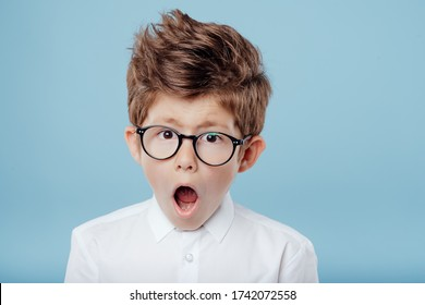 Stylish amazed little child with brown eyes in white shirt and eyewear standing with open mouth on blue background and looking at camera