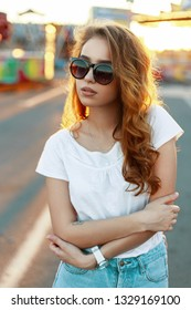 Stylish american redhead young hipster woman in trendy sunglasses in a t-shirt in vintage jeans posing on the background of the carousels in the park on a warm sunny day. Cute girl enjoys the weekend.