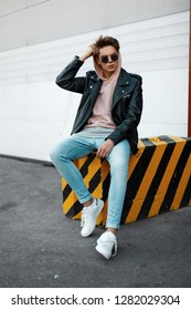 Stylish American young hipster man in a pink sweatshirt in trendy sunglasses in a leather jacket in jeans in white sneakers sitting on a striped concrete slab against a white gate. Cool guy