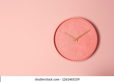 Stylish analog clock hanging on wall, space for text. Design with living coral color