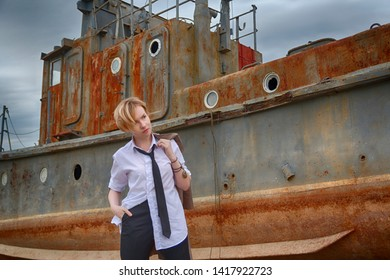 Stylish androgynous woman with short blond hair (bob haircut) in a white men's shirt, tie, pants and coat in her hand stands against the background of an old rusting ship
