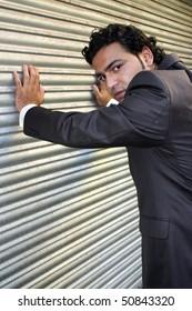 A stylish angry businessman posing near a shutter.