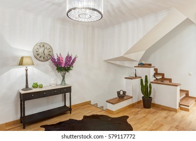 Stylish antechamber with wooden stairs to the second floor. Corridor with wooden table, watch over, black rug on the floor, violet flowers and flowers pot with cactus.