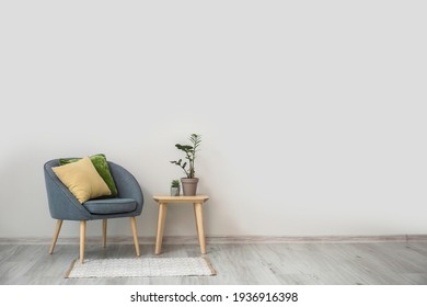 Stylish armchair with pillows, table and houseplants near light wall in room