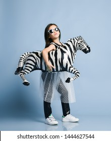 Stylish asian baby girl kid in high fashion clothes and sunglasses going to event birthday party with zebra metallic balloon under her arm on blue background