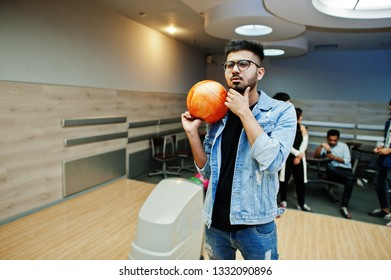 Stylish asian man in jeans jacket and glasses standing at bowling alley with ball at hand.