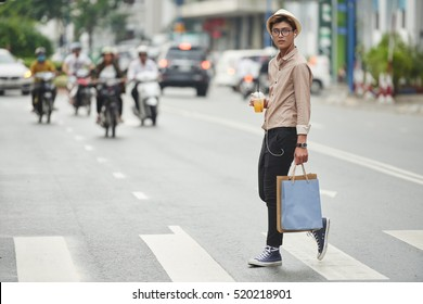 Stylish Asian man with shopping bags crossing the road