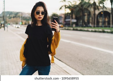 Stylish asian woman with long dark hair in sunglasses wearing blank black t-shirt and yellow leather jacket taking selfie by a mobile phone while standing on a blurred urban background.