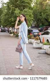Stylish asian-caucasian woman on a walk in european city in smart casual outfit and glasses. She has a break from her work