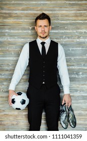 Stylish athletic man in a business costume vest holding a soccer ball with football boots. Against the background of a loft wall. Fashionable hairstyle and black tie. Coach or football player. Self