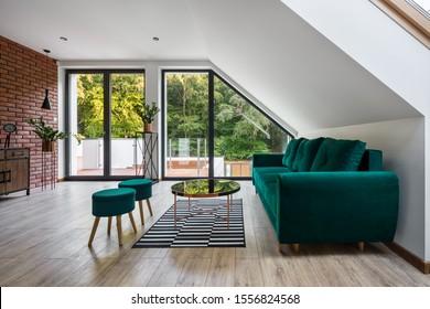 Stilvolles Wohnzimmer mit Ziegelwand, smaragdgrünem Mobiliar und Holzfußboden