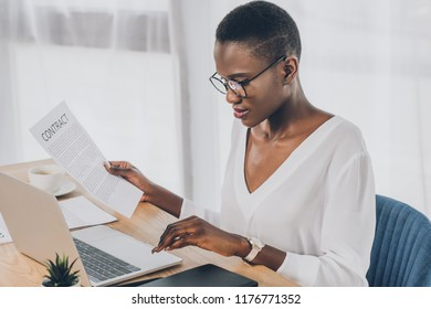 stylish attractive african american businesswoman holding contract and using laptop in office