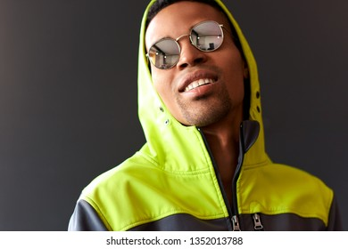 Stylish attractive African American man smiling and looking through mirror sunglasses, wearing green sport hoody, posing on black studio wall. People, emotion and lifestyle concept