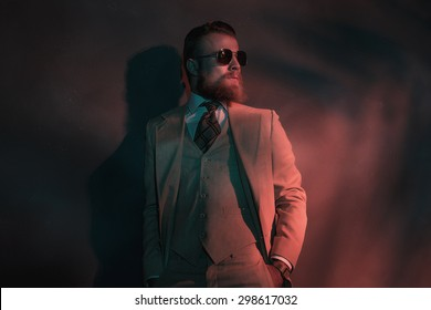Stylish attractive bearded man enjoying the night life standing in red toned lighting leaning against a wall wearing a suit and sunglasses