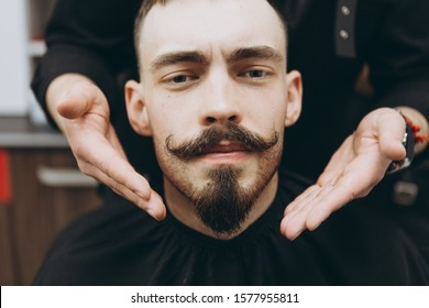 stylish attractive man with a beard in a barbershop. Shaving and modeling a contemporary beard shape in retro style, the barber shaves his client