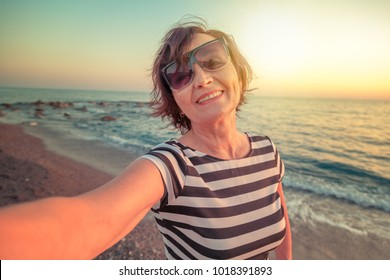 stylish attractive mature woman 50-60 makes selfie on mobile phone on the seashore, travel and retirement, fashion and beauty