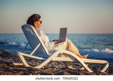 stylish attractive mature woman 50-60 makes use of laptop on the seashore, travel and retirement, fashion and beauty, active elderly people