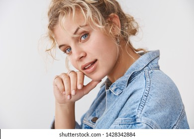 Stylish attractive sassy blond blue eyed young 20s woman wearing denim jacket turning cheeky flirty camera touch chin give smug smirking delighted have interesting plan, standing white background