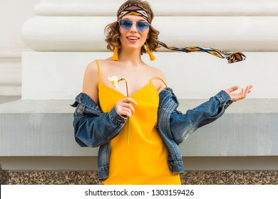 stylish attractive woman in hippie style outfit, yellow dress denim jacket, trendy accessories, sunglasses, smiling, happy positive mood, street fashion, spring summer fashion trend, cheerful emotion