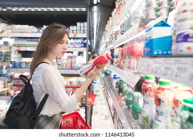 Stylish attractive woman is standing by the refrigerator with dairy products, holds yogurt in his hands and reads the label. An attractive girl buys a yogurt in a supermarket.