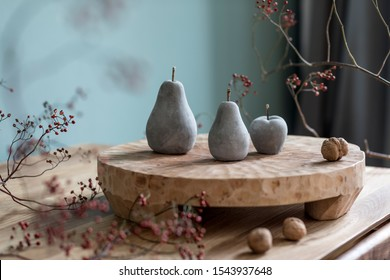 Stylish autumn composition of home decor on living room with wooden fruit tray, cement fruits, nuts and autumn flwoers. Eucalyptus color concpet. Template. Modern decoration. Close up.