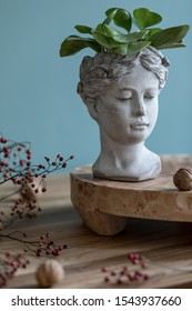 Stylish autumn composition of home decor on living room with wooden fruit tray, cement head sculpture, plants nuts and autumn flwoers. Eucalyptus color concpet. Template. Modern decoration. Close up.
