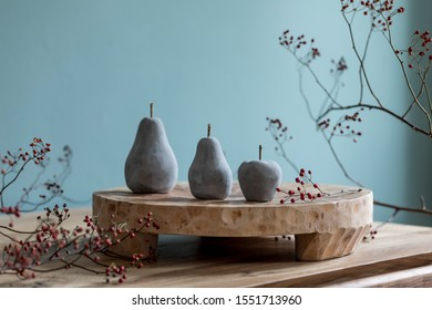 Stylish autumn composition of home decor on living room with wooden fruit tray, cement fruits and autumn flwoers. Eucalyptus color concpet. Template. Modern decoration. Close up.