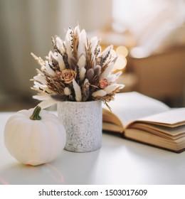 Stilvolles Herbstflach. Saisonale Herbstdekoration mit getrockneten Blumen und weißem Kürbis. Thanksgiving-, Halloween- und Herbstkonzept. Gemütliches warmes Bild, hellrosa Stil