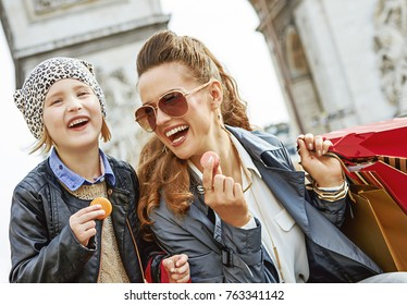 Stylish autumn in Paris. smiling trendy mother and daughter with shopping bags near Arc de Triomphe in Paris, France eating macaroons