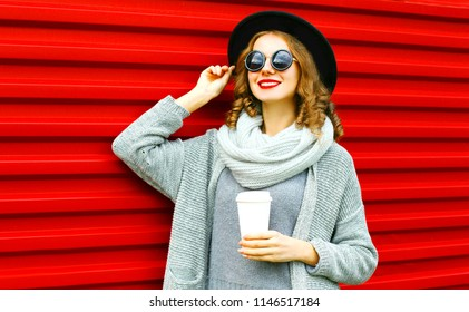 Stylish autumn portrait smiling woman with coffee cup is wearing a knitted clothes on a red background