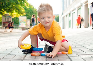 Stylish baby boy with blond hair in the yellow t-shirt and in red shorts. He sits near a shopping center and plays with a pyramid. Hipster style. Sunny weather. Outdoor shot