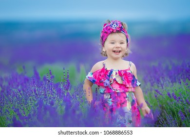 Stylish baby girl 2-3 year old walking in lavender field. Wearing rustic colorful dress and hat. Looking at camera.Smiling joking.