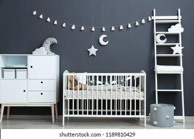 Stylish baby room interior with comfortable crib