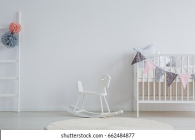 Stylish baby room with white vintage rocking horse