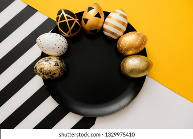 Stylish background with Easter golden decorated eggs on black plate. Trendy flat lay easter concept. Happy Easter card with copy space for text. Minimal easter concept. Striped and yellow background.