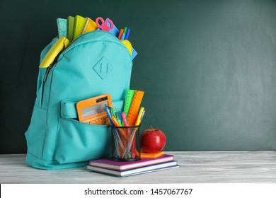 Stylish backpack with different school stationary on white wooden table at green chalkboard. Space for text