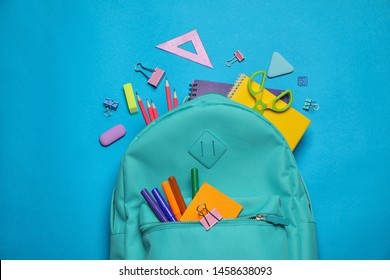 Stylish backpack with different school stationary on blue background, top view